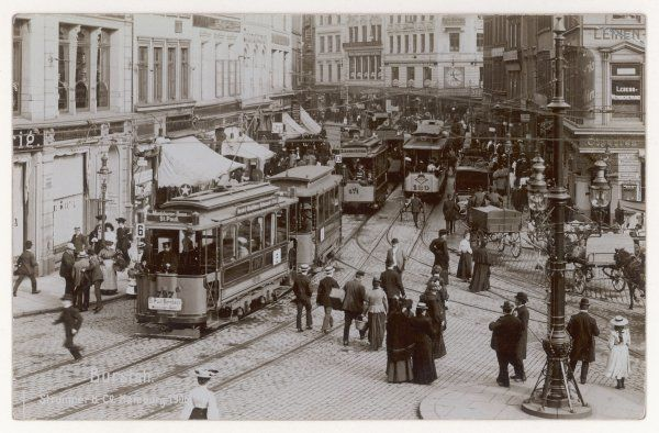 Trams dominate this busy scene in the centre of the city : a young girl and her father wait for a chance to cross the street between the many horse drawn vehicles