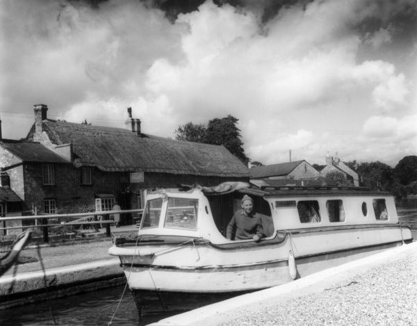 A happy man on a motor cruiser in the lock at Stoke Bruerne, Grand Union Canal, Northamptonshire, England, with its old thatched 'Boat Inn', a famous hostelry. Date: early 1960s