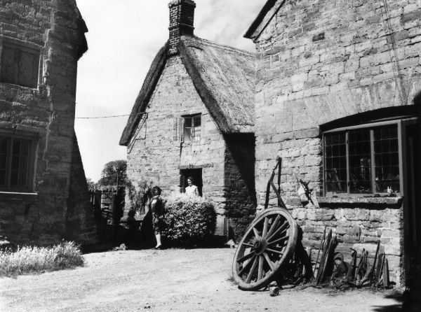 A corner of the stone-built village of Harlestone, Northamptonshire, England, with a glimpse of its old 'smithy' (blacksmiths). Date: late 1950s