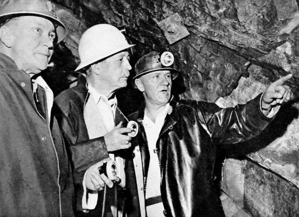 Photograph showing (Maurice) Harold Macmillan (1890-1986) (centre, in white helmet), then British Prime Minister, taking a tour of a South African gold mine, 28th January 1960. Date: 1960