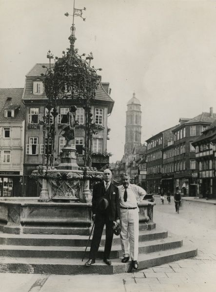 "Undated photograph of Harry Price and C. E. M. Joad standing in front of the ""Goose Girl"" fountain in Gottingen, during the trip for the black magic experiment conducted by Harry Price on the Brocken, Germany (the ""Brocken Experiment"")"