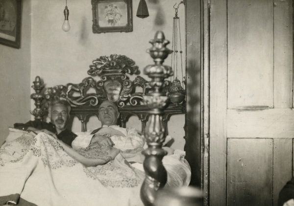 Photograph of Harry Price and C. E. M. Joad lying in and investigating a sixteenth-century carved walnut bed, alleged to be haunted, at a private museum in Chiswick, 15 September 1932. HPG/1/12/2