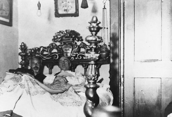 Psychical researcher and author, investigating an allegedly haunted 16th century bed in Chiswick, with professor Joad, 15 September 1932