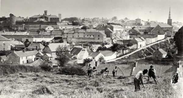 Harvest workers in a field above the town of Haverfordwest, Pembrokeshire, South Wales