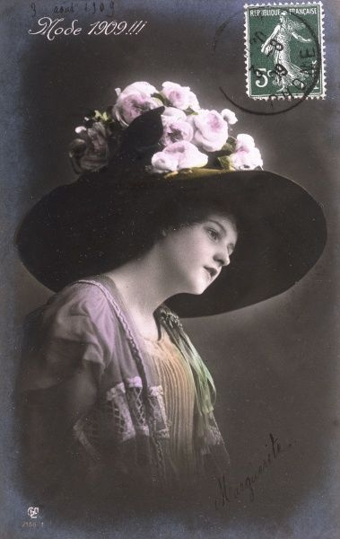 A woman named Marguerite in the fashionable hat for 1909 - a large creation with a broad brim & a high crown adorned with pink roses. Date: 1909