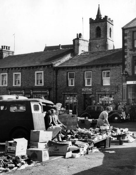 The shoe stall, a market day scene at Hawes, Yorkshire, England, with the tower and its church in the background. Date: late 1950s