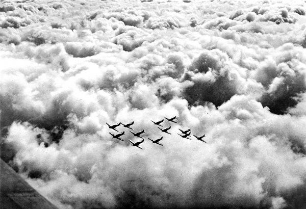 Photograph showing a squadron of British Hawker 'Hurricane' fighter airplanes flying in a tight formation, somewhere over Britain in 1940