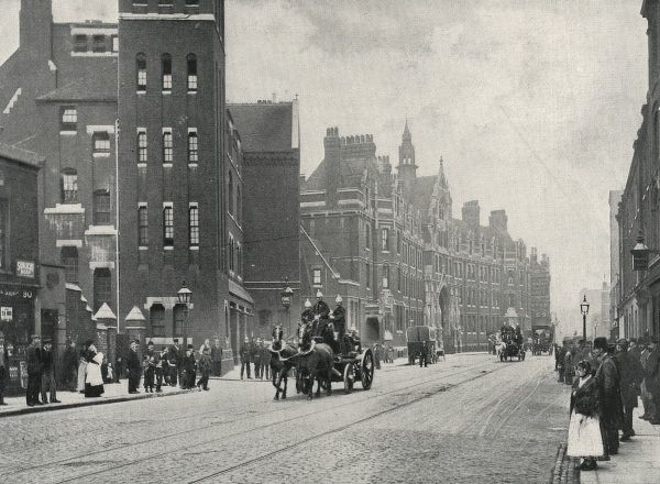 The headquarters of the London Fire Brigade on Southwark Bridge Road, with two horse-drawn fire engines passing in front, and passers by standing on both pavements