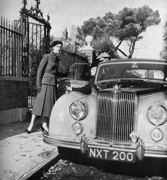 A woman enters a magnificent looking Armstrong Siddeley Sapphire saloon car wearing a dark grey barathea suit with flapped pockets set at an angle and a well-cut straight hanging skirt with plenty of room about it provided by three inverted pleats