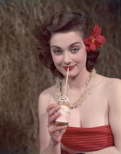 Brunette model with a red hibiscus flower in her hair, a white shell necklace and a low cut red striped, strapless bathing costume, sips soft drink from a pop bottle