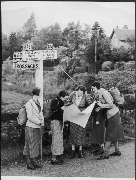 Four female holiday makers who are hiking through the Scottish countryside stop and check their route by a signpost at a crossroads in Kilmarhog, near Callander