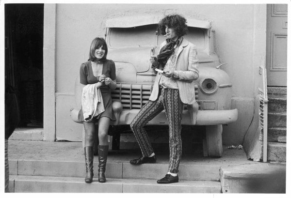 She wears a scoop neckline mini-dress and knee high boots; he is more outrageous in brightly patterned drain- pipe hipster trousers, silk scarf and lounge jacket