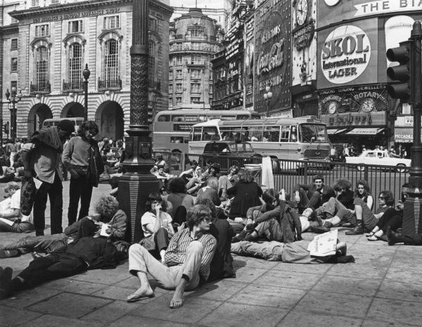 HIPPIES Hippies gather at Piccadilly Circus and sit around on the pavement in the sun. Date: 1969