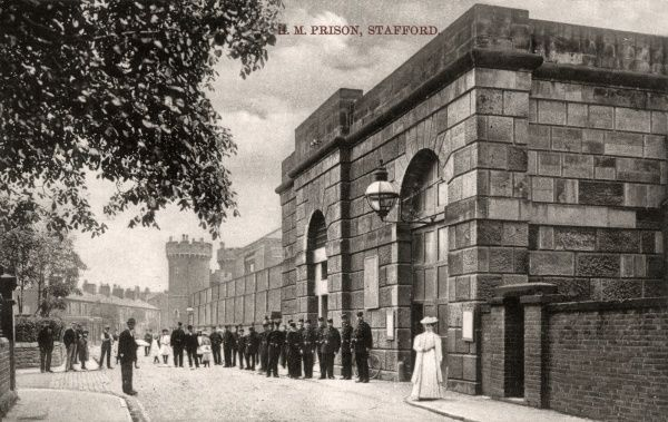 A view of Stafford prison in Staffordshire. A group of uniformed prison officers stand in front of the building