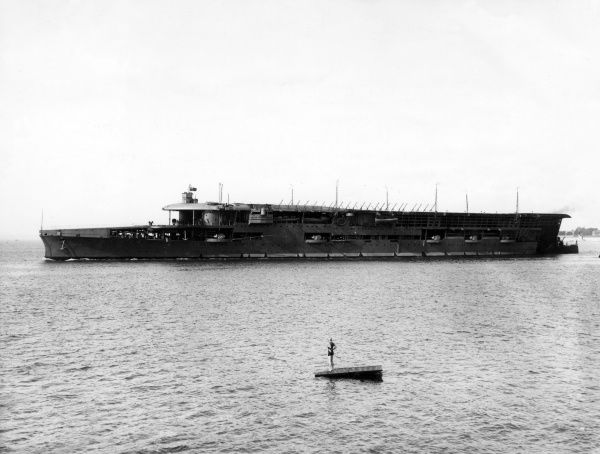 The aircraft carrier HMS Furious (a modified Courageous-class cruiser) during the First World War. Launched in 1916, HMS Furious served in both World Wars and was scrapped in 1948. A woman stands on a diving platform in the foreground. Date