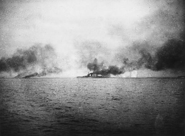 Scene during the Battle of Jutland, in the North Sea near Denmark, during the First World War, showing the British battlecruiser HMS Lion being hit on the Q turret, with 13th Flotilla torpedo boat destroyers working ahead to attack the enemy ships