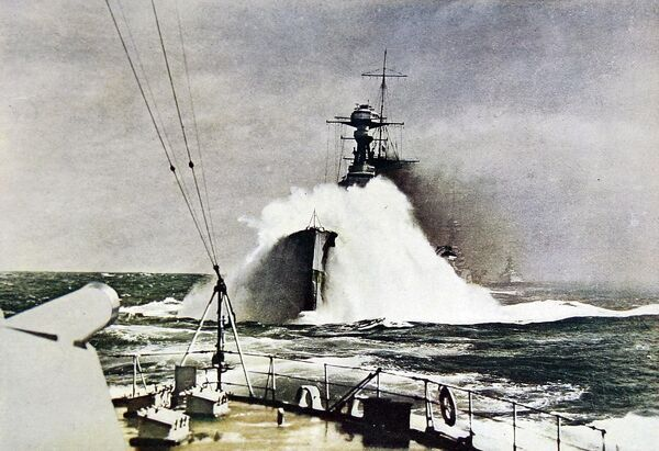 Photograph of a huge wave breaking over the bows of HMS 'Royal Oak', launched 1916, as seen from the stern of HMS 'Queen Elizabeth', Mediterranean Sea, 1935