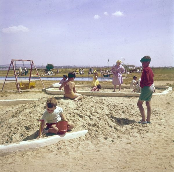 Children playing in the sand at a British holiday camp. Date: early 1960s