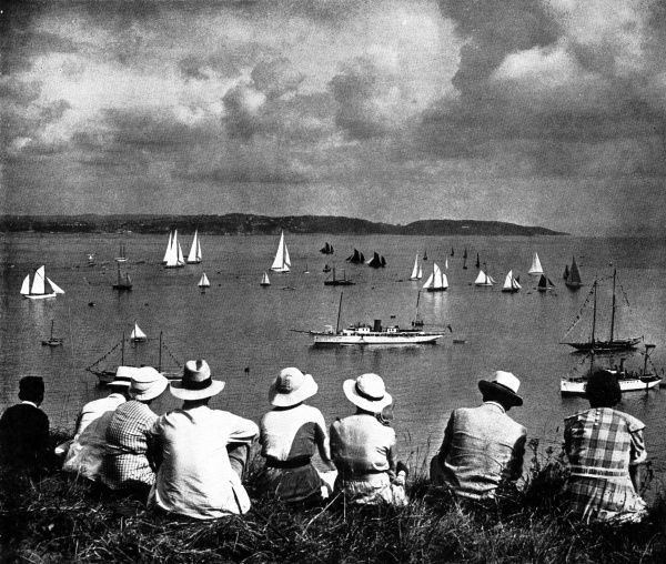 Photograph showing a group of holidaymakers watching the Brixham Regatta, from a vantage point on a West Country cliff, 1936. A number of fishing trawlers, with dark sails, share the waters with the white sails of racing yachts