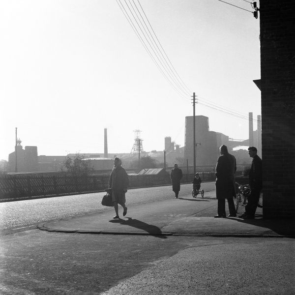Village life in Heath, Derbyshire, England. A lone woman, a young girl on a tricycle with her father beside her, and a couple of men chatting. Behind them, the outline of Holmewood Colliery in the early morning sun. Holmewood Colliery closed in1970