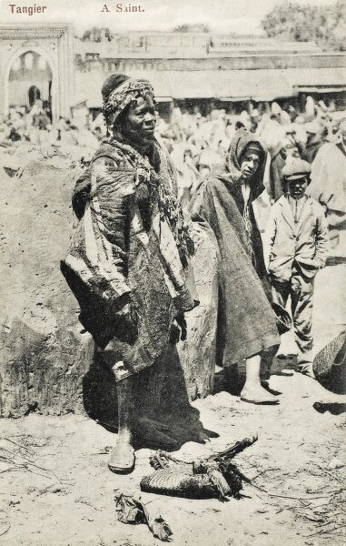 A Holy Man, Tangiers, Morocco ('Saint') standing in a Market, attracting a small crowd. Interestingly a young boy stands alongside in shabby Western attire