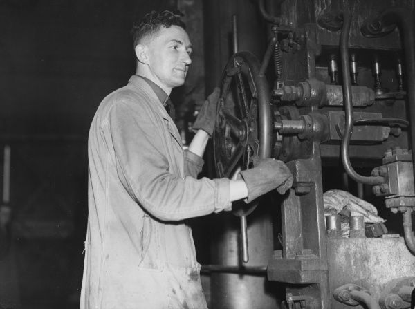 A member of the Home Guard working as a Press Operator on a 1500 ton press as part of the war effort on the home front during World War II
