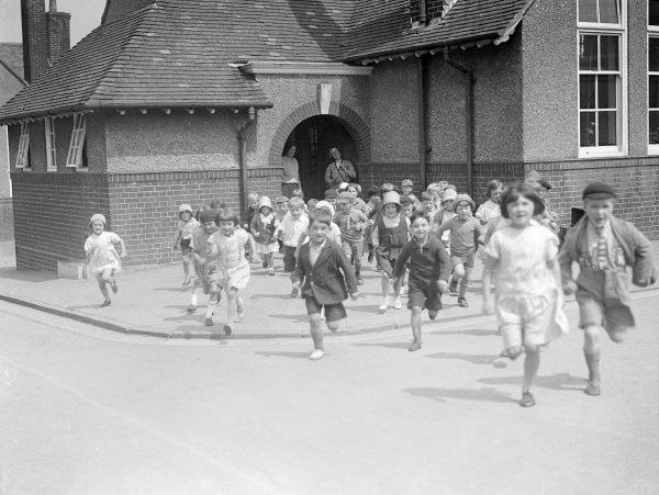 School's out! A group of happy schoolchildren running out of school at the end of the day. Date: 1930s
