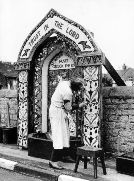 A Well Dressing at Hope, Derbyshire, England, which takes place on Acension Day. This ceremony is a relic of the old pagan custom of blessing wells for water. Date: 1950s