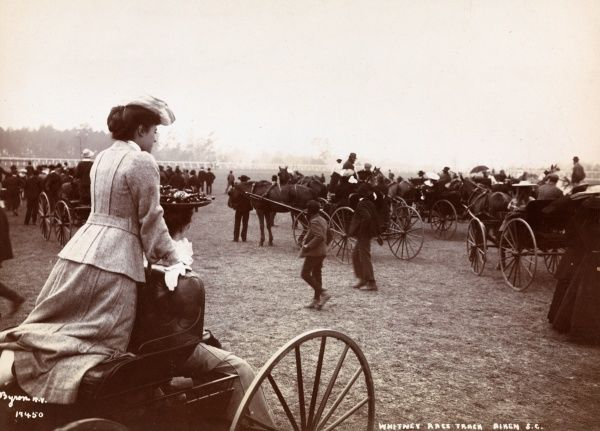 Whitney Race Track, Aiken S.C., America. Two women sitting in a carriage, overlooking a crowd of people, horses and carriages at the Whitney Race Track