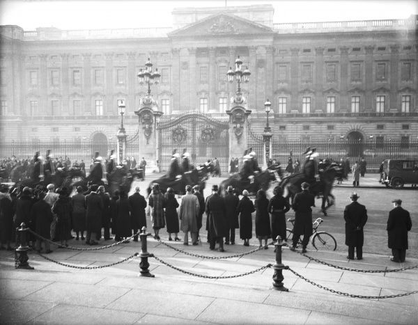 A crowd watching a horseguard procession outside Buckingham Palace, London, returning to Whitehall