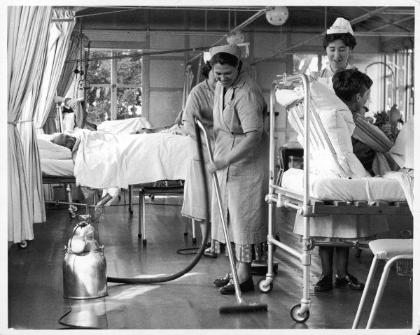 A nurse wheels a patient forward in his metal bed so that the daily Ward Maids can clean and polish the floors at Queen Mary's Hospital, Sidcup, Kent, England