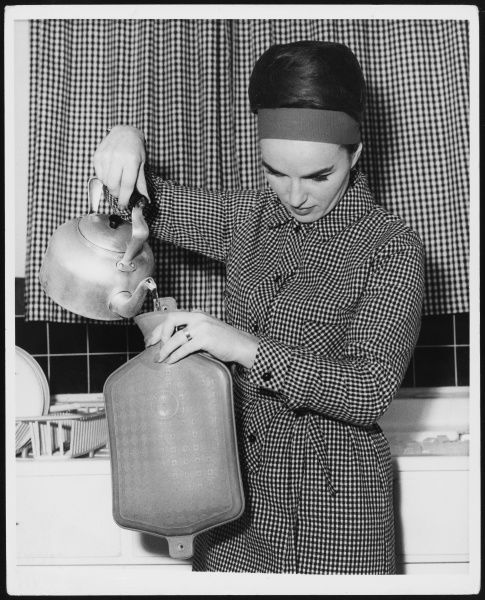 A smartly dressed woman fills her hot water bottle from a kettle