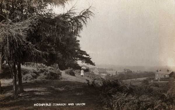 A view of Hothfield Common near Ashford, Kent. A girl stands with a parasol. In the distance is the West Ashford Union workhouse, later Hothfield Hospital