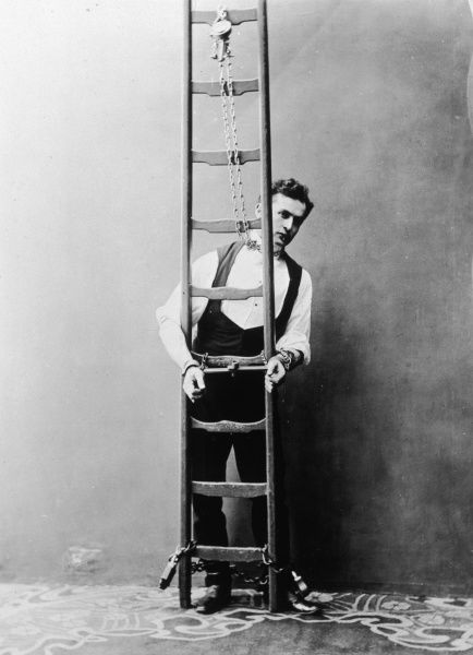 Harry Houdini chained by the neck, hands and feet to a ladder which would later be submerged in water