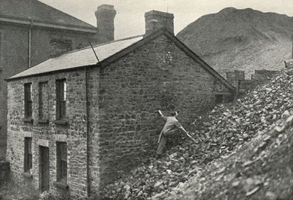 A house near Swansea is becoming overwhelmed by a nearby slag heap. A man clambers up the heap to inspect its progress. Date: circa 1936