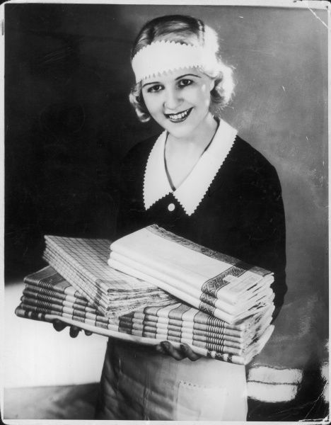 A smiley housemaid carrying freshly laundered and ironed tableware