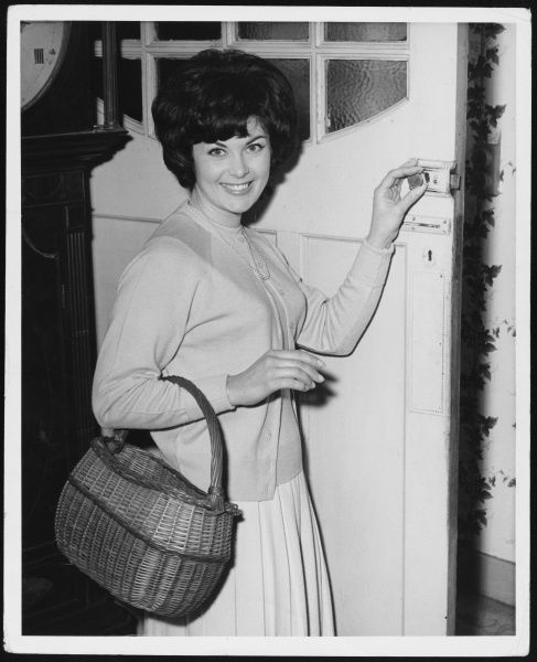 A young housewife smiles as she opens the front door before going shopping with her basket over her arm
