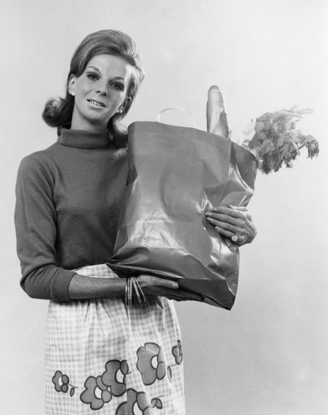 A woman with a big bag of groceries. Date: late 1960s