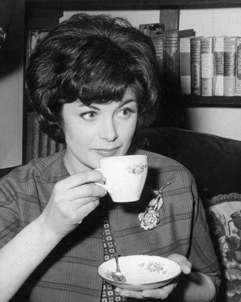 A smart housewife takes time out to enjoy a cup of tea in a china teacup and saucer. Date: 1960s