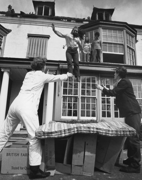Housewife Teresa Vincent leaps from the first floor of a building onto cardboard boxes and mattresses 20 feet below. 'It makes a change from washing up', she explained. Date: 1960s