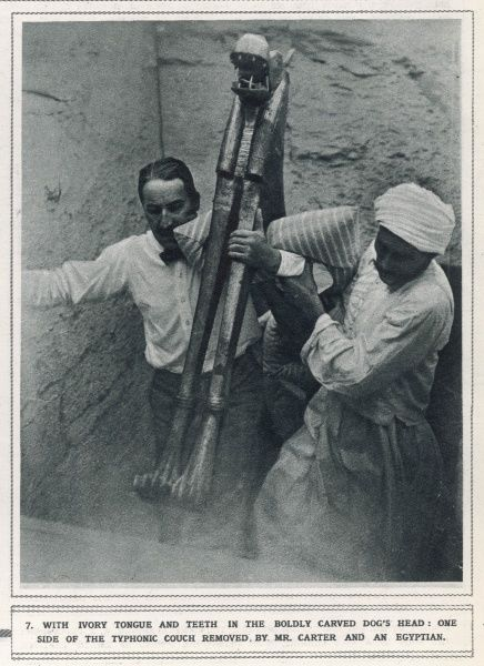 The photograph shows Howard Carter and an Egyptian removing the Typhonic Couch from the Tomb of Tutankhamun