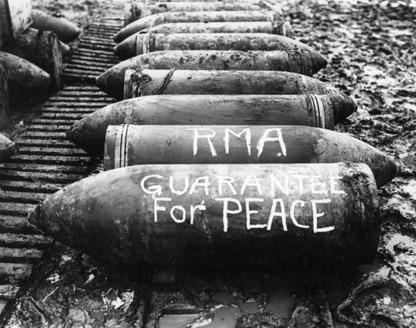 A line of 15 inch Howitzer shells on the muddy ground near Ypres, Belgium, during the First World War. Written on them are painted the initials RMA [Royal Marine Artillery] and the words Guarantee For Peace. Date: November 1916