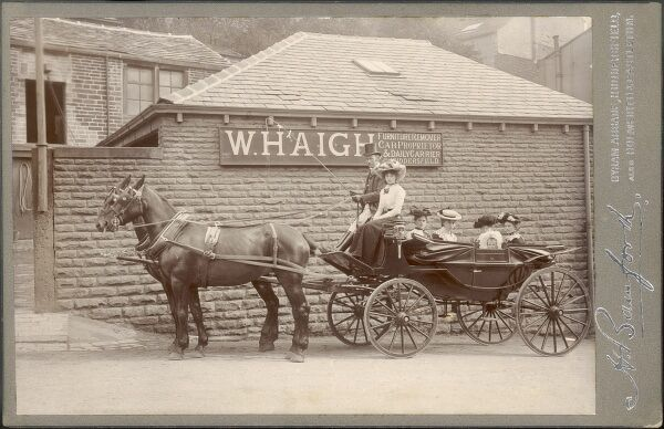 A fine photograph of an equally fine horse-drawn cab, with an open soft top, driven by the proprietor of the firm, W Haigh. Mr Haigh specialised in furniture removals, cabs and as a 'Daily Carrier'. The cab contains a group of women