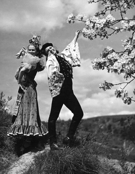 Two Hungarian dancing girls in flouncy traditional costumes, one in a dress, the other in trousers. Date: 1930s