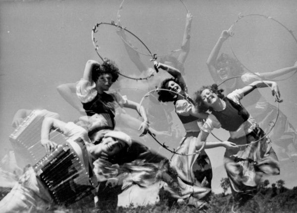 Hungarian girls performing a frenzied hoop dance to the wild strains of an accordion! Date: 1930s