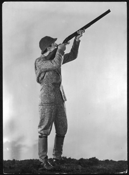 A sportsman in tweed suit, high leather boots with elasticated, water-proof spatterdashes and a tweed helmet hat