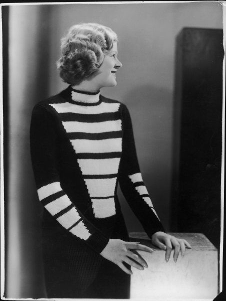 Unusual hand-knitted pullover modelled on a Huzzar's uniform incorporates a bold geometric pattern of light coloured bands of diminishing length on bodice & sleeves