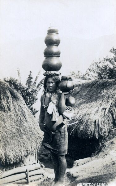 Igorote woman carring water pots and a baby. Igorot are the people of the Cordillera region, on the Philippino Island of Luzon. The smaller group of the Igorot live in the east and north of the Island and formerly practiced headhunting