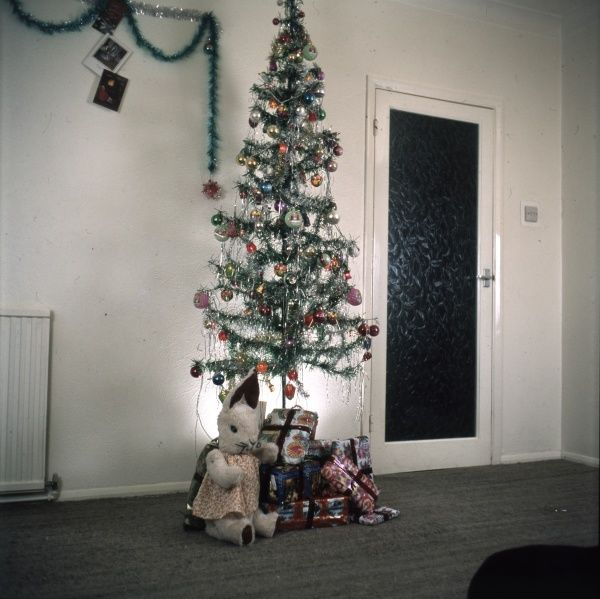 An imitation Christmas tree, with a cuddly toy and assorted presents underneath it