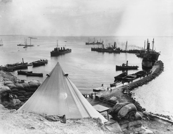 The improvised harbour at Lancashire Landing on W Beach. It was constructed of grounded ships, and proved a highly successful haven from the heavy seas experienced in this area. A British Destroyer is here seen in the harbour